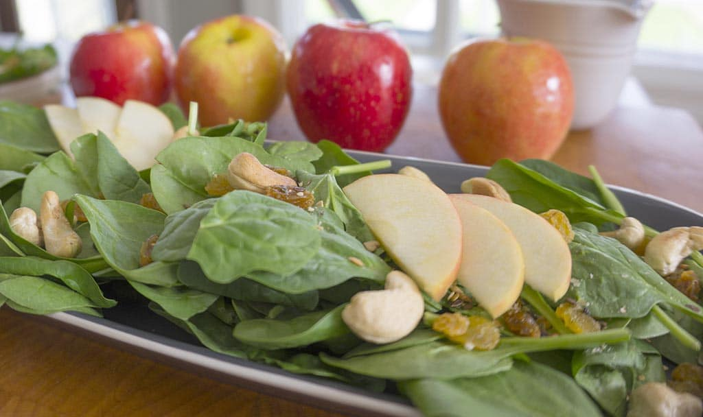 Apple-Cashew Spinach Salad on plate with apples in background