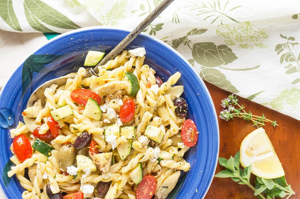 Lemon, Garlic + Herbs dress this one-pot Greek Pasta Salad with creamy French feta cheese, olives, artichokes and zucchini! | PASTA | ZUCCHINI | VEGETARIAN | GREEK | Recipe at OatandSesame.com