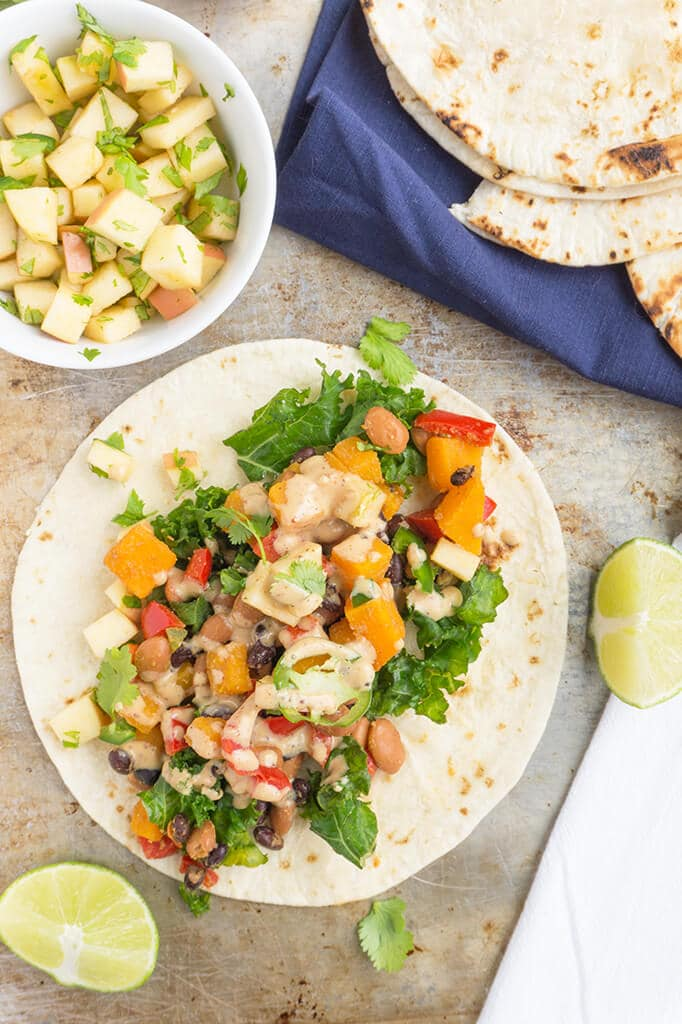 These Vegetarian Tacos with Black Beans are loaded with seasoned vegetables, topped with apples and finished with a smoky maple dressing for a seasonal twist. TacoTuesday should always be this healthy and delicious! | TACOS | VEGETARIAN | VEGAN | PLANT BASED | Recipe at OatandSesame.com
